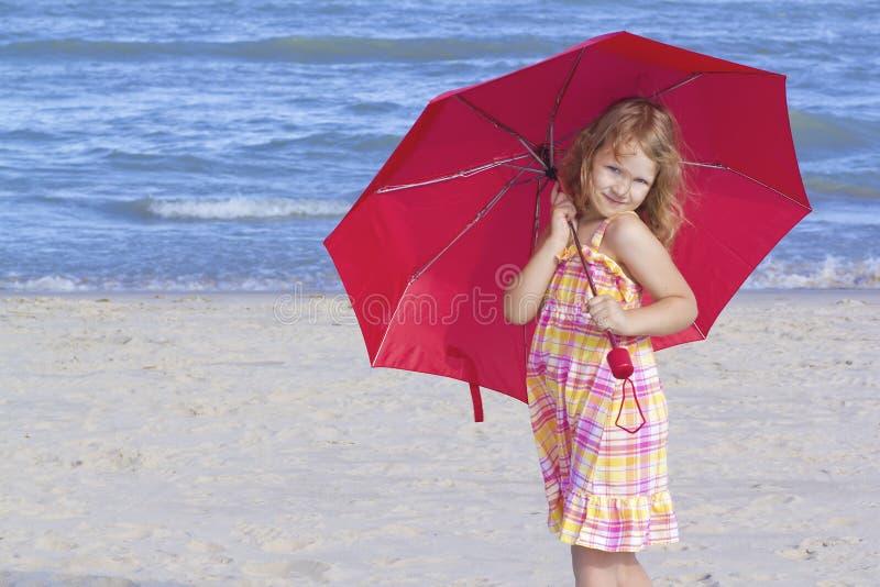 Enfant retenant un parapluie rouge à la plage photographie stock
