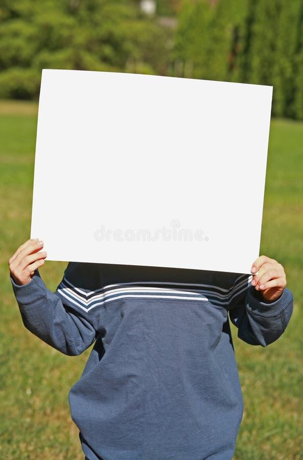 Enfant retenant un signe blanc photographie stock
