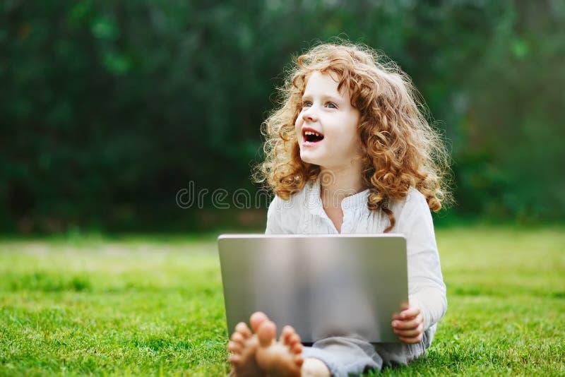 Enfant riant travaillant avec le carnet sur la pelouse verte dans le pair d'été photographie stock