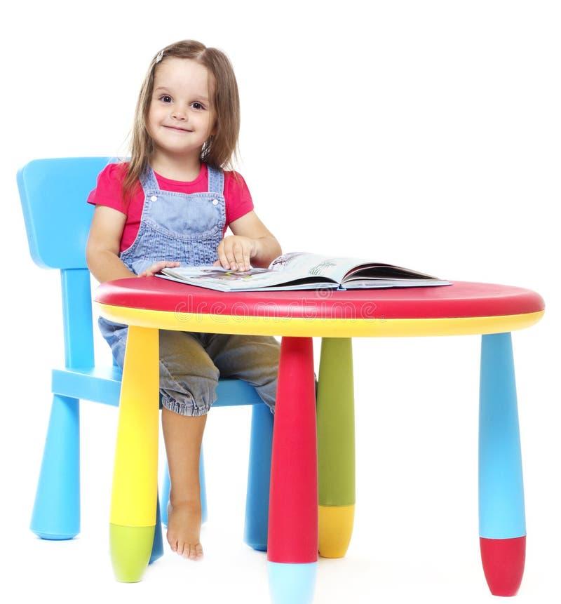 Enfant s'asseyant à la table et lisant un livre photo libre de droits