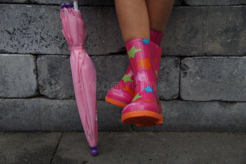 Enfant s'asseyant avec des jambes dans des bottes en caoutchouc tenant un parapluie photos stock