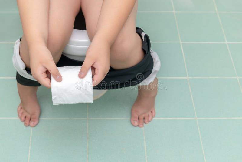 Enfant s'asseyant dans la toilette et tenant le petit pain de tissu photos libres de droits