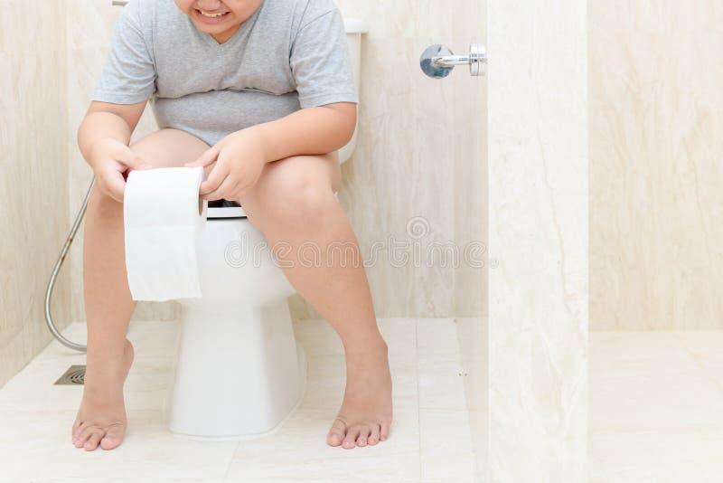 Enfant s'asseyant dans la toilette et tenant le petit pain de tissu images libres de droits