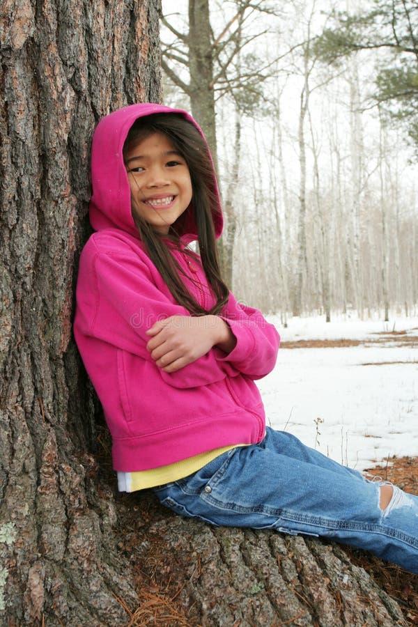 Enfant s'asseyant sous l'arbre en hiver images libres de droits
