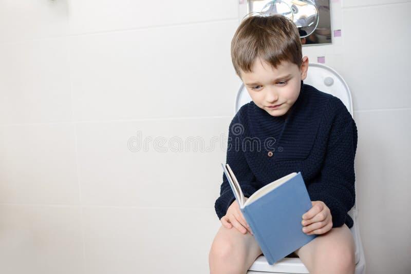 Enfant s'asseyant sur la toilette et lisant un livre image stock