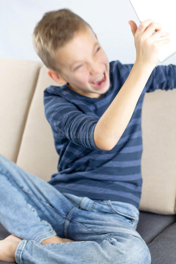 Enfant s'asseyant sur le divan et à l'aide de la tablette Cris contrariés et frustrés de garçon de l'adolescence avec colère tout images stock