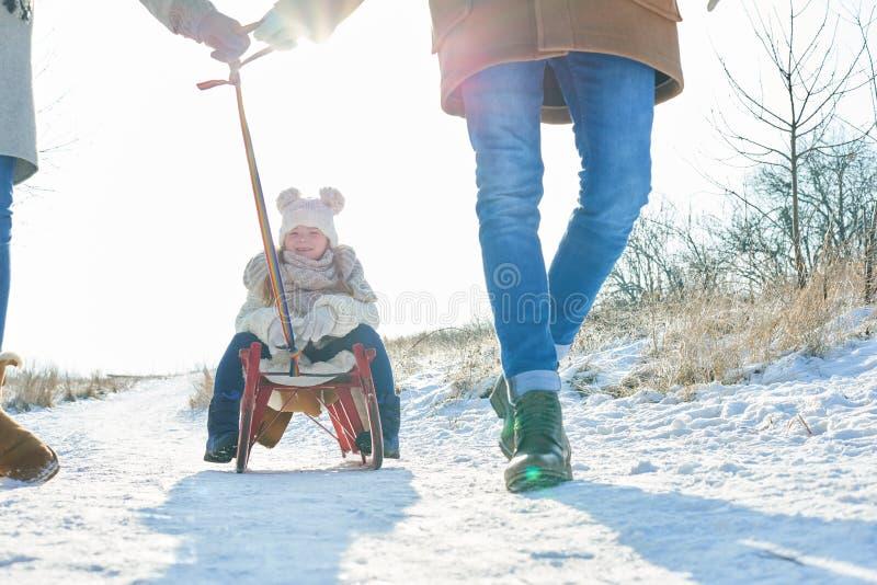 Enfant s'asseyant sur le traîneau et conduisant sur la neige photographie stock