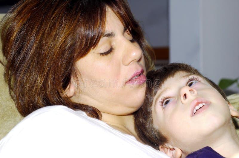 Enfant s'asseyant sur les genoux de mamans photographie stock
