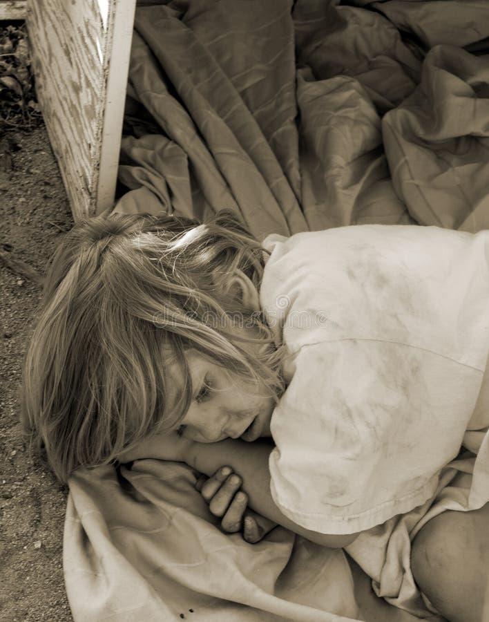 Enfant sans abri fixant dans une vieille boîte photos libres de droits