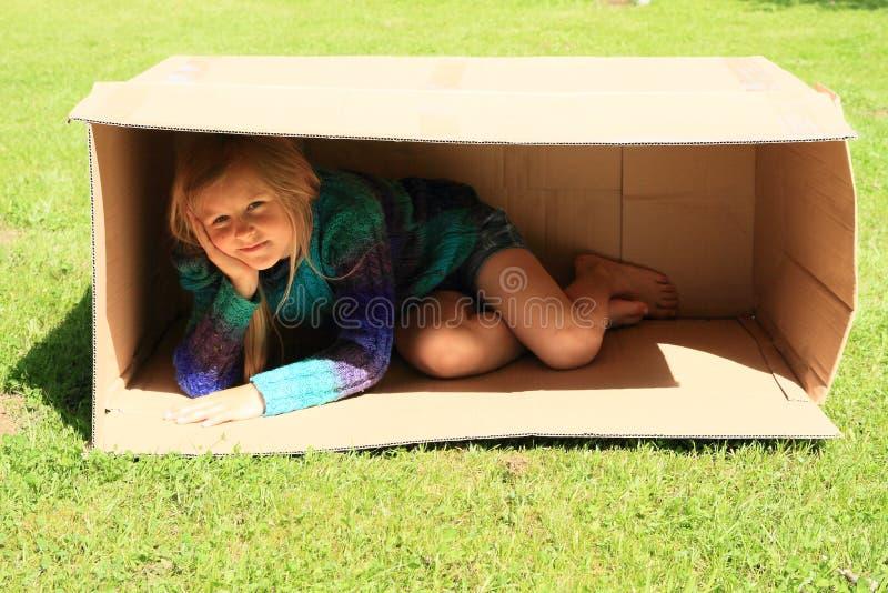Enfant se cachant dans la boîte photos stock
