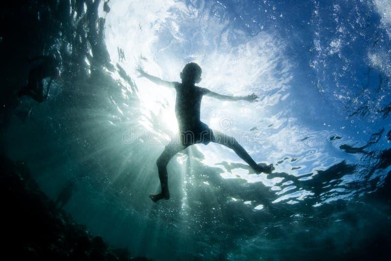 Enfant silhouetté dans l'océan pacifique photo libre de droits