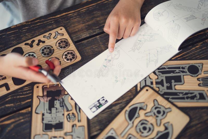 Enfant soigneux suivant les instructions et jouant avec le constructeur photo libre de droits