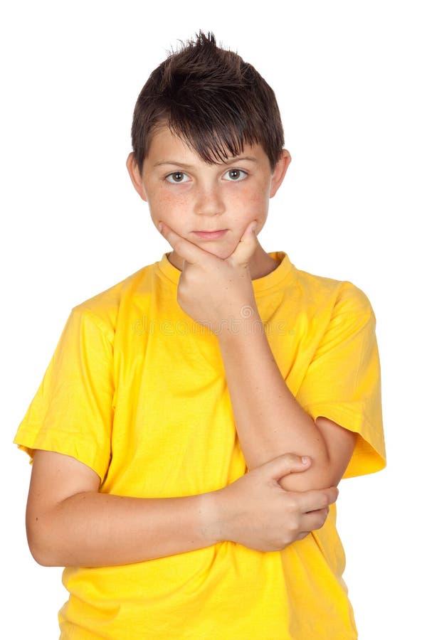 Enfant songeur avec le T-shirt jaune images stock
