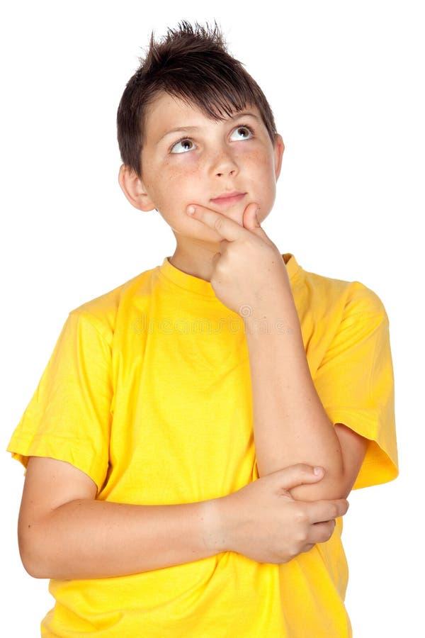 Enfant songeur avec le T-shirt jaune photo libre de droits