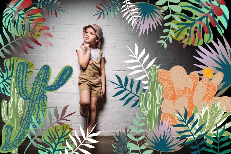 enfant songeur dans le costume de safari se tenant au mur blanc illustration stock