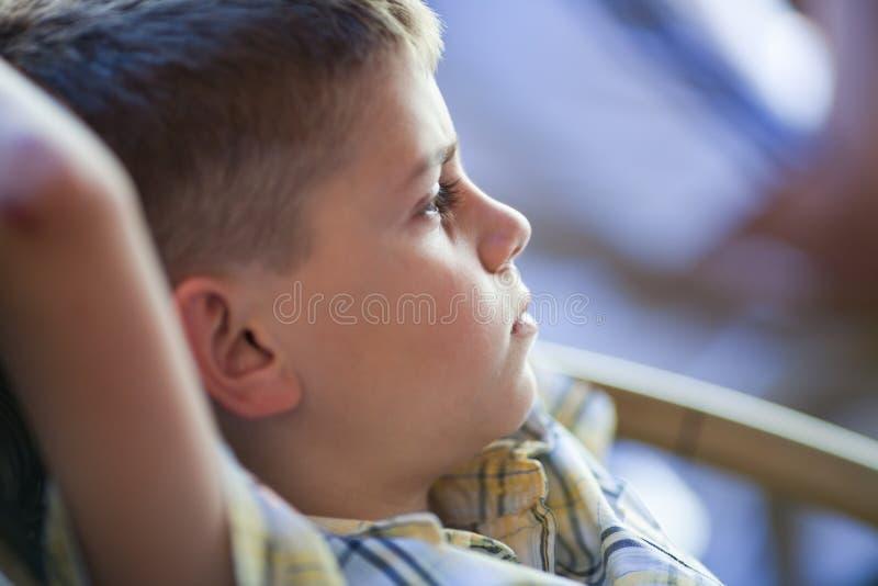 Enfant songeur s'asseyant avec des mains derrière la tête image libre de droits