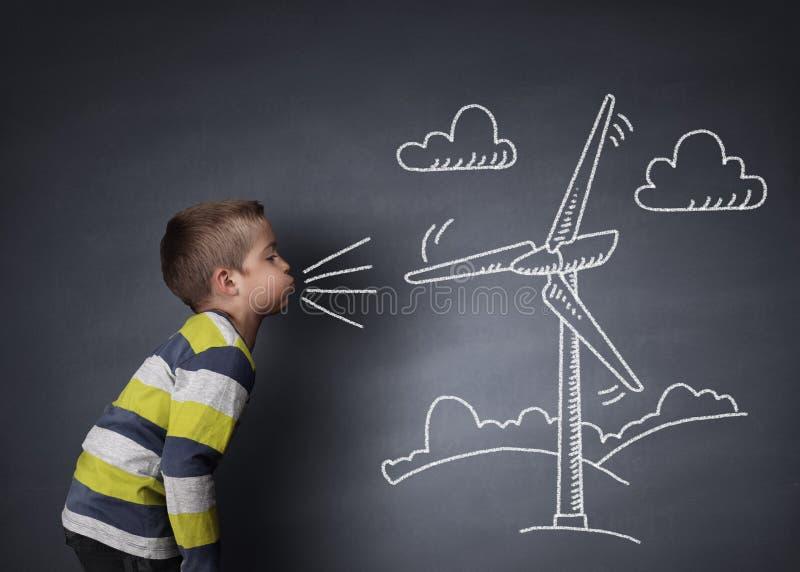 Enfant soufflant une turbine de vent de craie image libre de droits