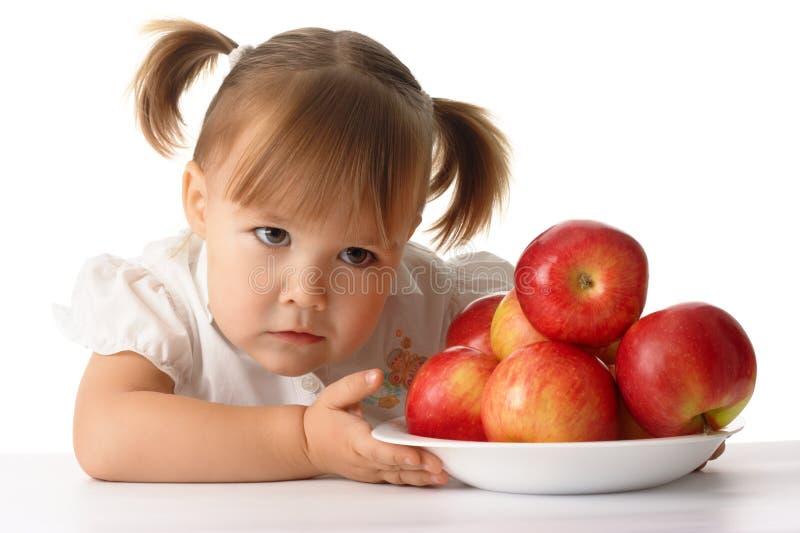 Enfant soupçonneux avec des pommes image libre de droits