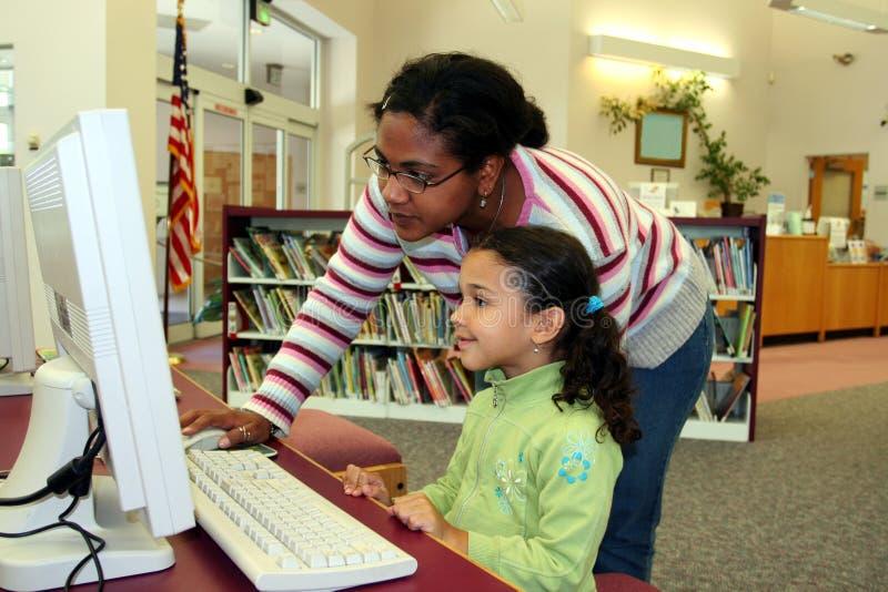 Enfant sur l'ordinateur avec le professeur images stock