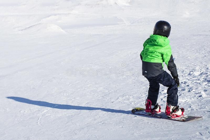 Enfant sur le surf des neiges en nature de coucher du soleil d'hiver Photo de sport avec éditer l'espace photographie stock
