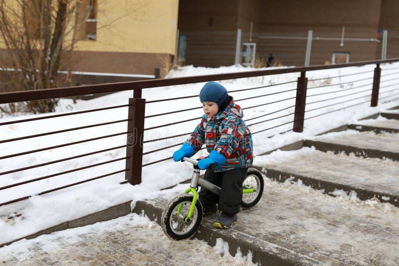 Enfant sur le vélo d'équilibre en hiver photos libres de droits