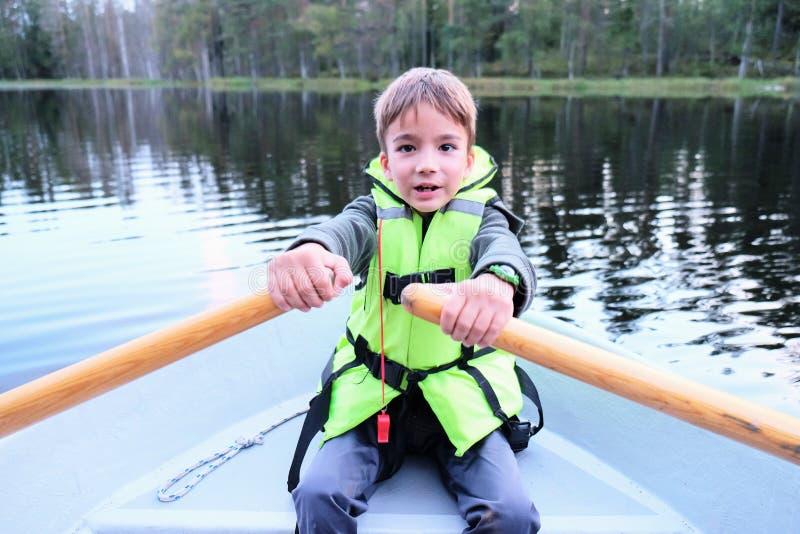 Enfant sur un bateau au lac de forêt photographie stock libre de droits