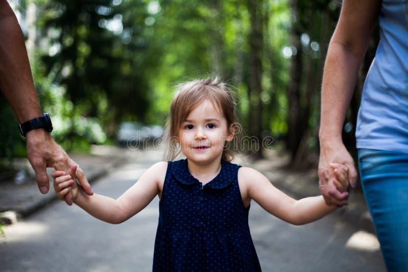 Enfant tenant des mains de parents en parc Enfance heureux images stock