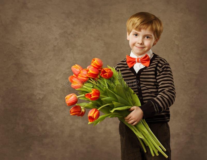 Enfant tenant le bouquet de fleurs de tulipes photographie stock