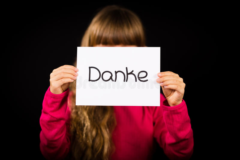 Enfant tenant le signe avec le mot allemand Danke - merci images stock