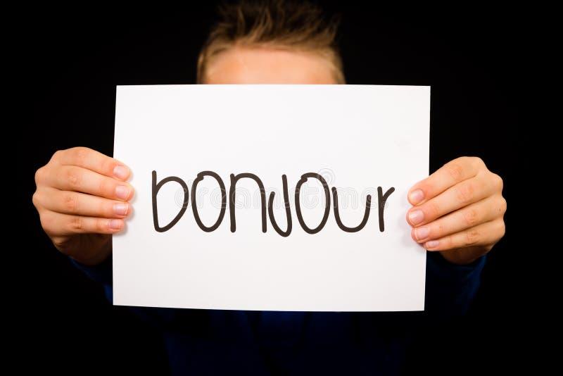 Enfant tenant le signe avec le mot français Bonjour - bonjour photographie stock