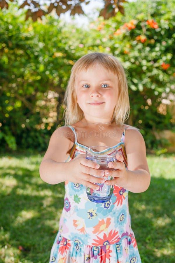 Enfant tenant le verre d'eau potable dehors photo libre de droits