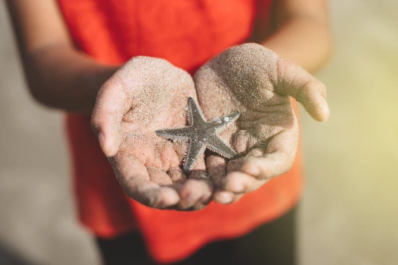 Enfant tenant ou montrant une étoile de mer dans une main évasée avec le sable de plage images libres de droits