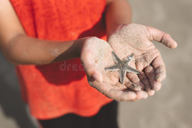 Enfant tenant ou montrant une étoile de mer dans une main évasée avec le sable de plage photographie stock libre de droits