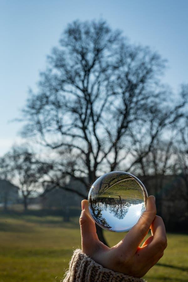 Enfant tenant une sphère en verre en parc en hiver photographie stock