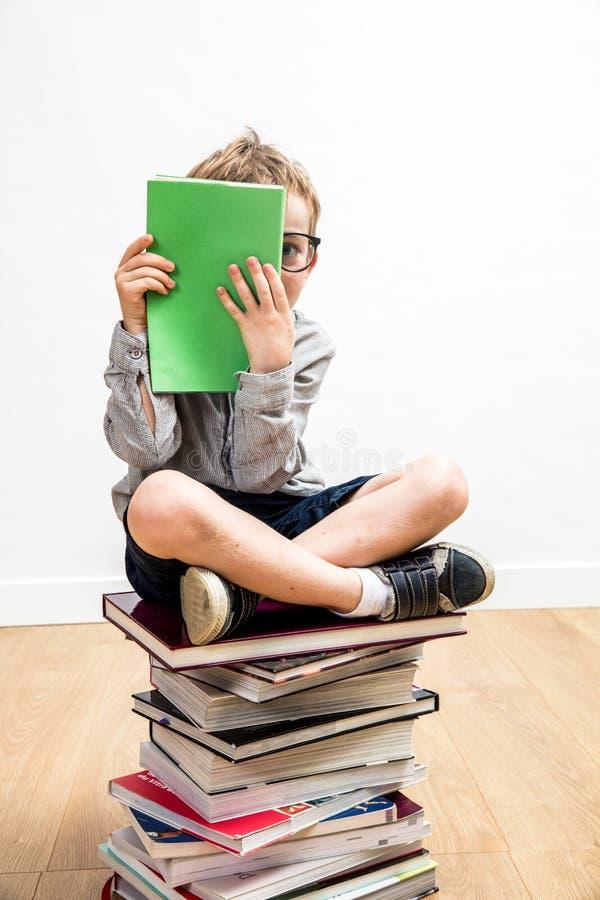 Enfant timide de rat de bibliothèque s'asseyant sur beaucoup de livres se cachant derrière le livre photographie stock libre de droits