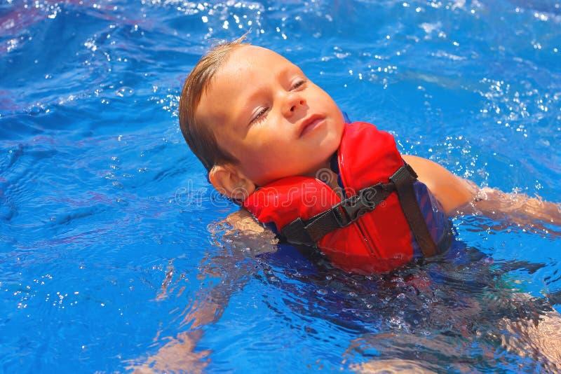 Enfant tranquille dans le gilet flottant sur elle de retour à la piscine image libre de droits
