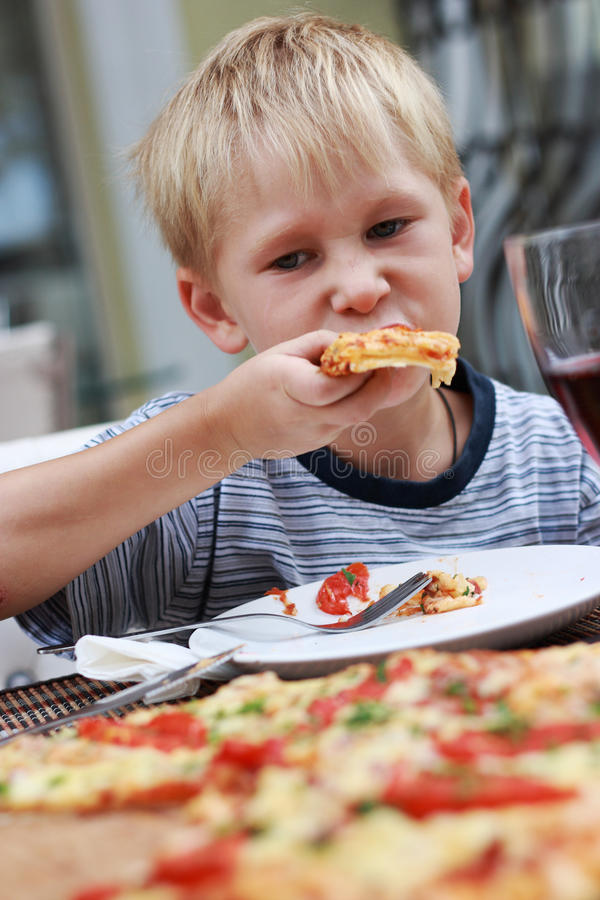 Enfant triste mangeant de la pizza. photos libres de droits