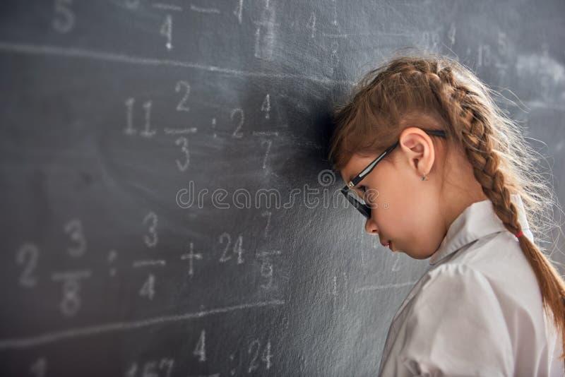 Enfant triste près du tableau noir photos stock