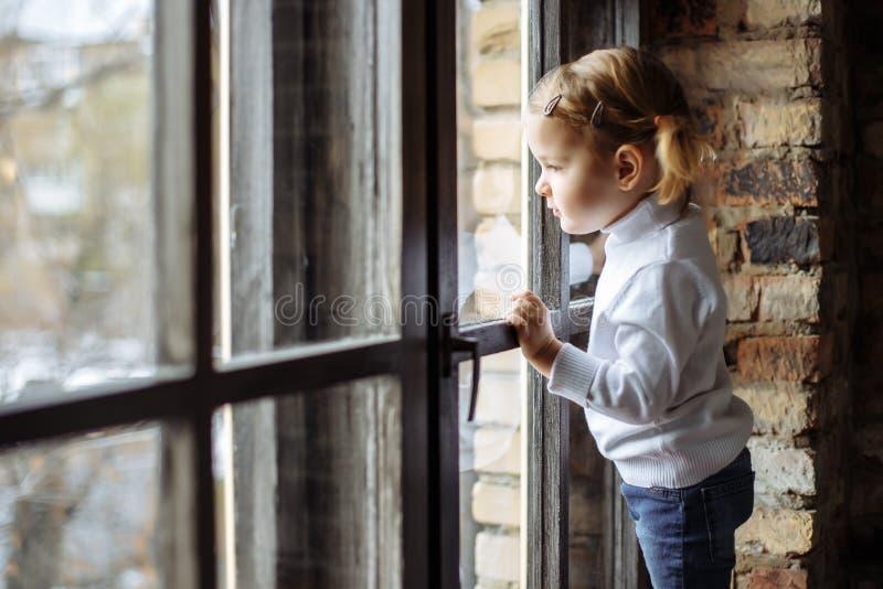 Enfant triste regardant la fenêtre photo stock
