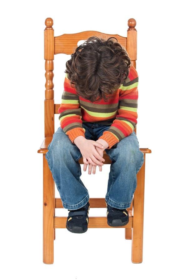 Enfant triste s'asseyant sur une présidence d'isolement photo stock