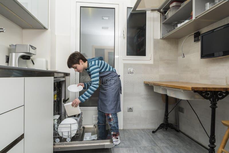 Enfant vidant le lave-vaisselle image libre de droits