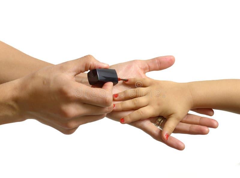 Enfantez appliquer le vernis à ongles à sa petite fille d'isolement photos stock
