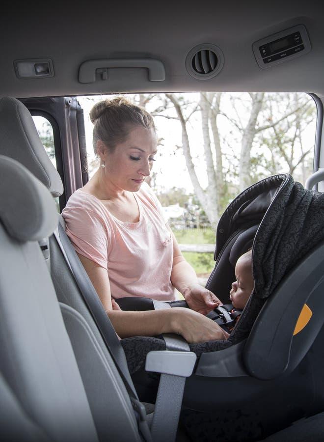 Enfantez attacher son enfant dans son siège de voiture correctement images libres de droits