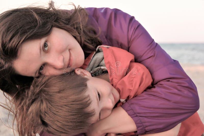 Enfantez caresser son fils, coucher du soleil sur le bord de mer photographie stock libre de droits