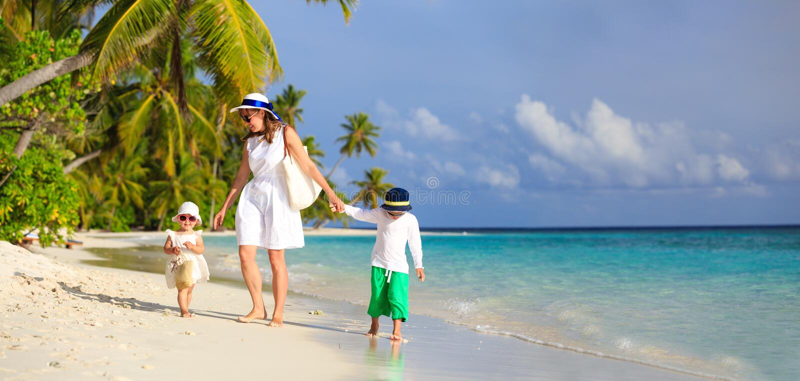 Enfantez et deux enfants marchant sur la plage tropicale images stock
