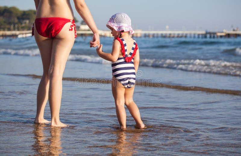 Enfantez et sa fille marchant sur la plage images stock