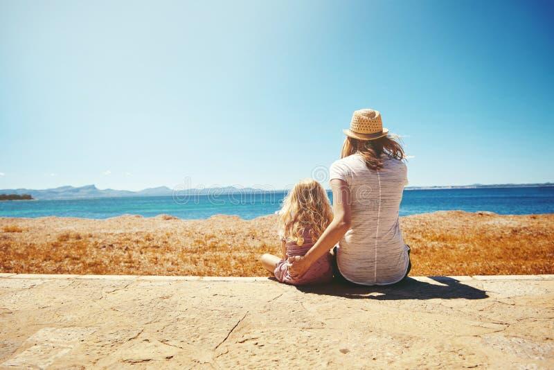 Enfantez et sa fille s'asseyant sur le bord de la mer photo stock