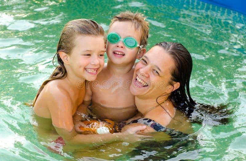 Enfantez et ses enfants dans la piscine images libres de droits