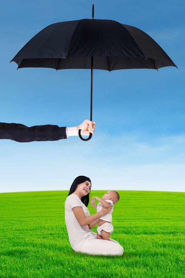 Enfantez et son bébé jouant sous le parapluie au champ photographie stock