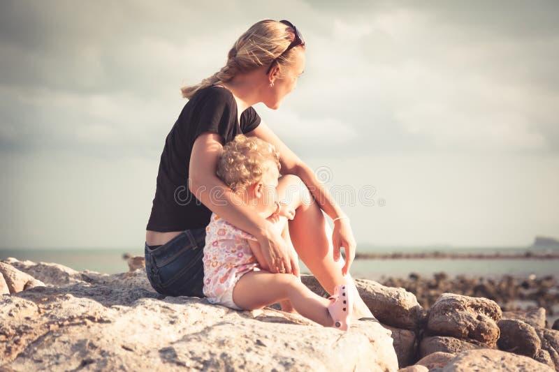 Enfantez et son bébé s'asseyant ensemble sur la côte de plage pendant le coucher du soleil et examinant la distance images stock
